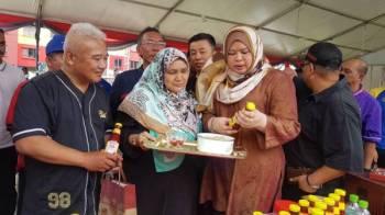 Rina melihat produk sos cili keluaran usahawan tempatan ketika melawat gerai pameran pada Program Komuniti Sejahtera di PPR Perkasa, Kuala Lumpur hari ini.
