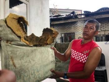 Penduduk yang dikenali sebagai Makhtar menunjukkan kusyen kerusi diletakkan di luar rumahnya yang terbakar Rabu lalu.
