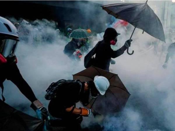 Polis Hong Kong turut melepaskan meriam air kimia dan gas pemedih mata kepada penunjuk perasaan yang melemparkan bom molotov di luar pejabat kerajaan Hong Kong. - Foto Reuters