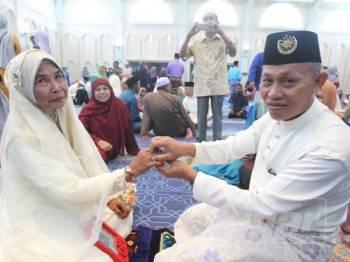 Muajam (kanan) menyarungkan cincin kepada Siti Habsah dalam majlis Nikah Jamaie Syarie di sini.