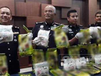 Zainuddin (dua dari kiri) menunjukkan dadah jenis syabu yang diletakkan di dalam bagi mengaburi pihak berkuasa.