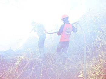 Anggota bomba kini berhempas-pulas mengawal kebakaran hutan di Kampar. - Foto: AFP