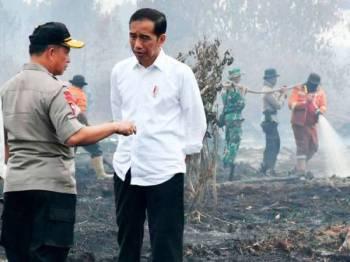 Jokowi ketika meninjau lokasi kebakaran hutan dan tanah pertanian di Merbau, Riau kelmarin.