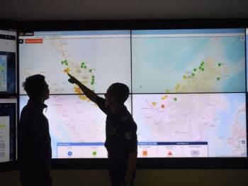 Petugas Agensi Pengurusan Bencana Negara Malaysia (NADMA) Nasrul Hadi Ishak (kanan) bersama Mohd Suhainizam Abdul Halim menunjukkan peta kitaran angin mengenai cuaca jerebu yang melanda negara ketika ini di Markas Pasukan Mencari Dan Menyelamat Khas Malaysia (SMART), NADMA hari ini. - Foto Bernama