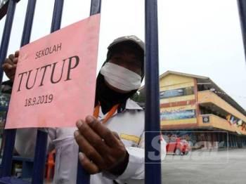 Pengawal keselamatan, Puan Norasiah meletakkan pengumuman penutupan sementara di Sekolah Kebangsaan Seksyen 17 Shah Alam ekoran jerebu teruk yang melanda negeri ini hari ini. - Foto ASRIL ASWANDI SHUKOR