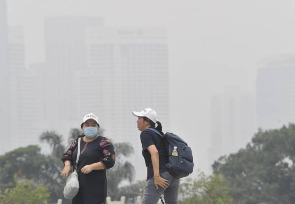 Pengunjung tempat awam memakai topeng muka berikutan keadaan yang berjerebu ketika tinjauan di Taman Tasik Perdana hari ini. -Foto Bernama