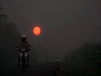 Pemandangan matahari kemerahan akibat jerebu dirakam di Jalan Sri Aman - Lingga, Sarawak. - Foto Bernama