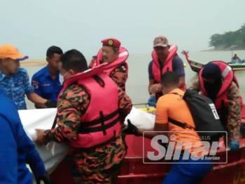 Anggota penyelamat mengangkat mayat mangsa yang ditemukan pagi tadi.