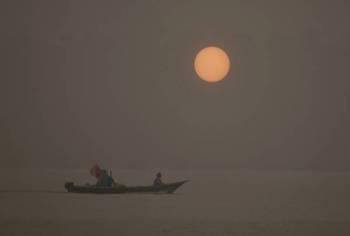 Sebuah bot nelayan kelihatan di pantai yang berlatarbelakangkan pemandangan matahari kemerahan akibat jerebu di Kampung Buntal yang terletak 30 kilometer dari bandaraya Kuching hari ini. -Foto Bernama
