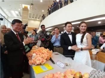 Kon Yeow (kiri) menyaksikan salah satu pasangan yang mendaftar perkahwinan di Fiesta Perkahwinan Beramai-ramai JPN Pulau Pinang tadi.