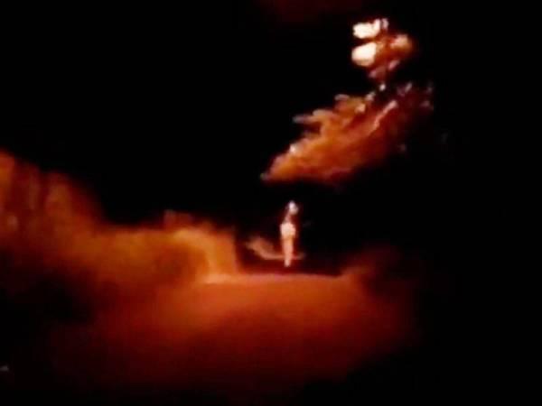 Tangkap layar video tular menunjukkan objek berwarna putih di tengah jalan yang dipercayai pocong.