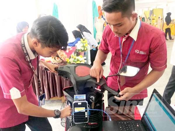 Adeeb Aideen (kiri) melihat 'fingerprint bike starter' yang dipasangkan Wan Amiruddin di motosikal.