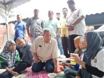 Mat Nadzari bertemu penduduk yang tinggal dalam khemah selepas rumah mereka dirobohkan bagi laluan projek pelebaran sungai di Paya Jaras Hilir, Sungai Buloh.