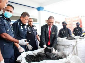 Abdul Hamid (tiga dari kiri) melihat sebahagian daripada 60 tan arang batu yang dicampur kokain.