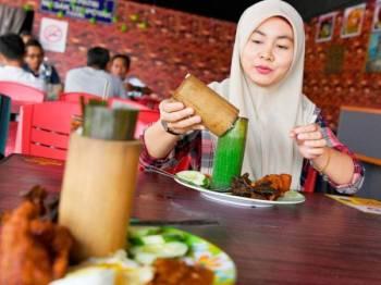 Pelanggan, Nurul Ain Nadhirah Basharludin, 30, teruja menikmati nasi lemak buluh. - Foto Bernama