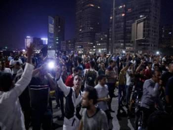 Kumpulan penunjuk perasaan melaungkan slogan menggesa al-Sisi melepaskan jawatannya. - Foto: AFP