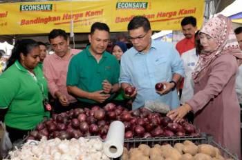 Saifuddin Nasution (dua dari kanan) melihat bawang besar yang dijual dengan harga RM1.99 sekilogram pada Majlis Pelancaran Fiesta Kempen Beli Barangan Malaysia Zon Utara di Tasik Darulaman Park, Bandar Darulaman, hari ini. Foto:  Bernama