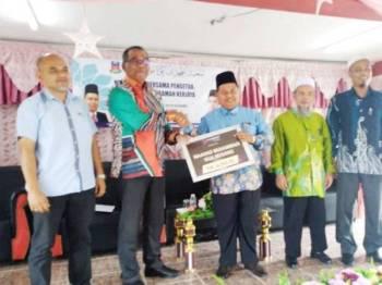 Mohd Zaki (kanan) menerima replika cek daripada Pengurus Bank Rakyat Gua Musang, Azhan Ahmed.