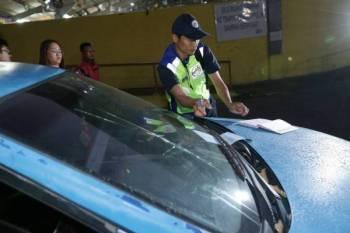 Anggota penguatkuasa MPHTJ meletakkan kompaun di kenderaan wanita terbabit ketika operasi bersepadu di Pasar Borong MPHTJ Batu Berendam di sini hari ini.