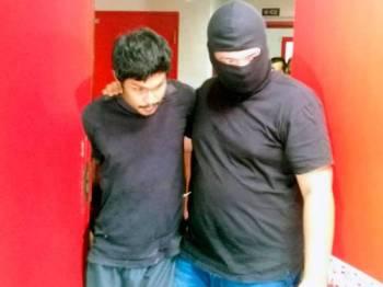 Mahadi (kiri) sewaktu diiringi polis dari Bahagian Antipengganas (E8) di Mahkamah Sesyen Kuala Terengganu. -Foto fail Sinar Harian