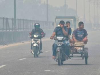 Penunggang motosikal terpaksa menutup hidung ketika melalui sebuah jalan di Kampar, Riau. -Foto AFP