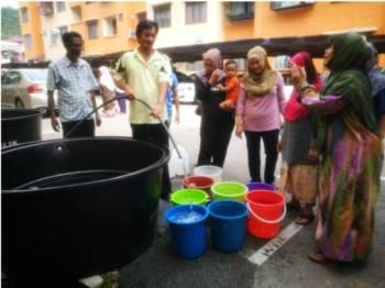 Penduduk Blok E Rumah Pangsa Pantai Peringgit sedang menunggu giliran untuk mengisi air.