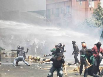 Polis anti rusuhan terpaksa menggunakan semburan air untuk menyuraikan peserta protes di Makassar, Sulawesi semalam. Foto: AFP