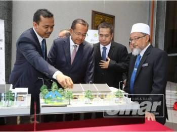 Ahmad Samsuri (dua dari kiri) melihat model rumah yang akan dibina selepas melancarkan Dasar Perumahan Baharu Negeri Terengganu di Wisma Darul Iman hari ini.