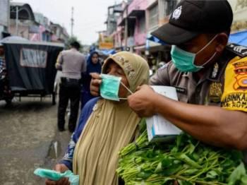 Anggota polis membantu seorang wanita memakai topeng di Banda Aceh semalam. - Foto AFP
