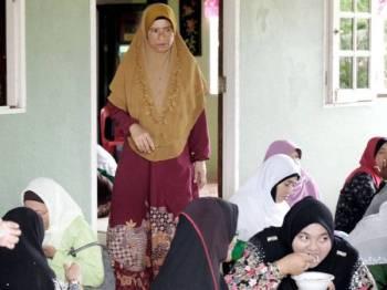 Ibu kepada Allahyarham Muhammad Adib Mohd Kassim; Asma Aziz, 52, (berdiri, tengah) melayani tetamu yang hadir pada Majlis Tahlil dan Bacaan Surah Yasin untuk Allahyarham di kediaman mereka di Kampung Tebengau hari ini. --fotoBERNAMA