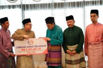 Sultan Sharafuddin Idris Shah berkenan menerima pembayaran zakat perniagaan QSR Brands (M) Holdings Berhad daripada Azahari (dua dari kiri) di Istana Bukit Kayangan di Shah Alam semalam.