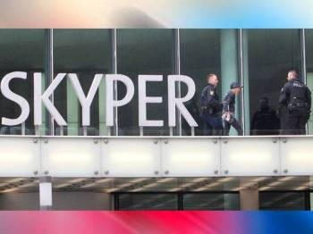Alain Robert atau 'Spiderman Perancis' (tengah) ditahan pihak berkuasa selepas memanjat Menara Skyper di Frankfurt am Main,Jerman hari ini. - Foto AFP