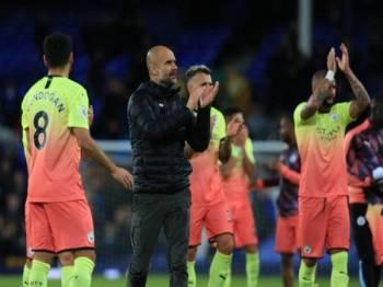 Aksi Guardiola ketika meraikan kemenangan bersama pemain Manchester City selepas menewaskan Everton di Goodison Park.