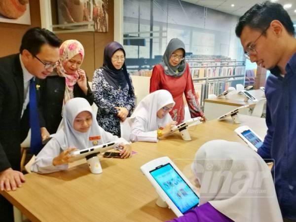 Maziah (berdiri, dua kanan) melihat pengguna yang menggunakan kemudahan pembacaan eBuku dilanggan PNM.