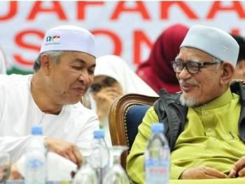 Ahmad Zahid (kiri) berkata sesuatu yang mencuit hati Abdul Hadi (kanan) sehingga kedua-duanya kelihatan tersenyum di pentas ceramah Muafakat Nasional UMNO-Pas di Dewan 2020, malam tadi. -Foto Pas Perlis