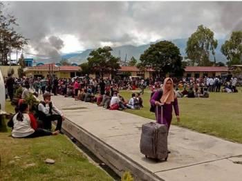Penduduk yang melarikan diri berkumpul di sebuah padang di Wamena susulan rusuhan yang berlaku di bandar itu. - Foto AFP