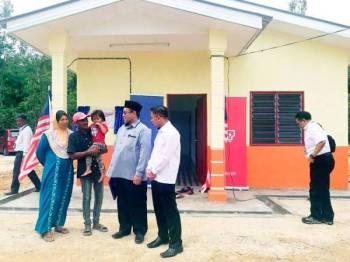 Rozlin (dua dari kiri) bersama Suhami (dua dari kanan) dan Farizan (kanan) di hadapan rumah baharu diterimanya melalui projek Baiti Jannati TNB.