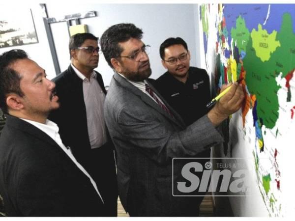 Nazir menurunkan tandatangan sambil diperhatikan Mohamad Raimi (kiri) dan Ketua Pegawai Eksekutif Global Peace Mission Malaysia, Ahmad Fahmi (kanan) dalam Perbincangan Meja Bulat: Peduli Kashmir. - Foto Asril Aswandi Shukor.