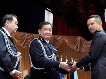Abdul Hamid (tengah) menyampaikan Ijazah Sarjana Sains Sosial (Pengajian Kepolisan) kepada Superintendan Mohd Hafiz Shamsudin (kanan) di Maktab Polis Diraja Malaysia hari ini. FOTO: BERNAMA