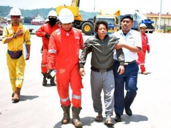 Nelayan Thailand yang diselamatkan dipapah semasa tiba di Pelabuhan Kemaman, tengahari semalam.