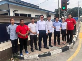 Tan Tiong Yih (empat, kanan) bersama pimpinan DAP negeri membuat laporan polis terhadap Najib atas kesalahan fitnah Nga Kor Ming, hari ini.