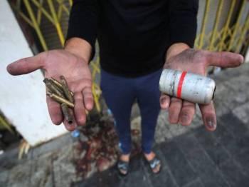 Penunjuk perasaan menunjukkan kelongsong peluru (tangan kiri) dan kanister gas pemedih mata (tangan kanan) yang dilepaskan pasukan keselamatan ketika siri protes yang bermula kelmarin. - Foto: AFP