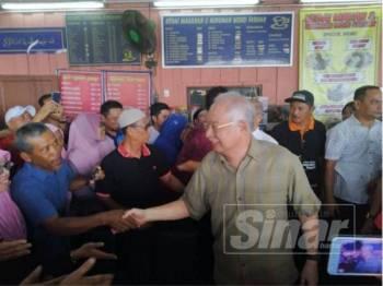 Najib bersalaman dengan masyarakat Tanjung Piai ketika bersarapan di Warung Farhan Kampung Rimba Terjun pagi tadi.