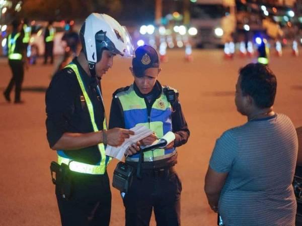 Penguatkuasa JPJ sedang memeriksa dokumen pengguna jalan raya dalam operasi itu, malam tadi.