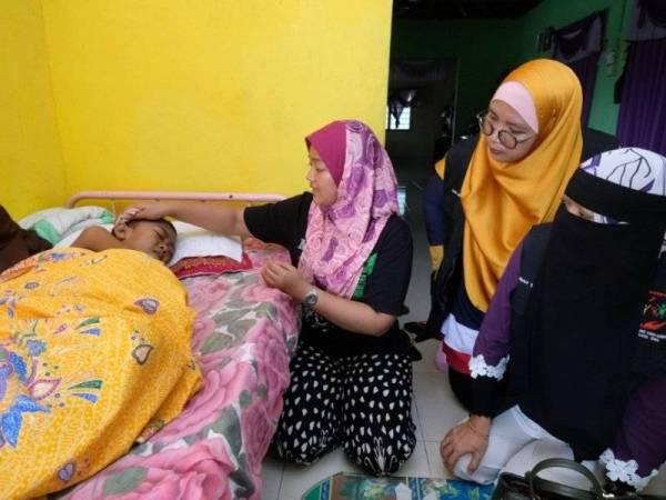 Nor Sakilawati (dua dari kiri) sedang mengelap kepala anaknya sambil diperhatikan oleh Maznah (kanan) di rumah mereka di sini hari ini.