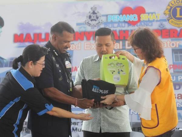 Afif (dua dari kanan) menyampaikan peranti AED kepada Narenasagaran di sini hari ini.