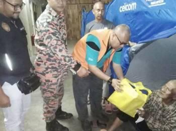 Shamsul Izrin mengagihkan bantuan kepada mangsa banjir yang terjejas. - Foto JKM