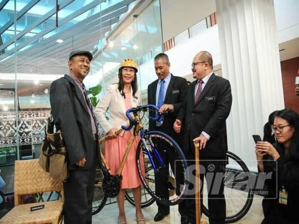 Teresa (dua dari kiri) mempamerkan basikal khas diperbuat daripada buluh tempatan di ruang pameran lobi Parlimen hari ini.