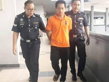 Tertuduh diiringi anggota polis selepas didakwa di Mahkamah Ayer Keroh di sini hari ini kerana didakwa mengugut ibunya.