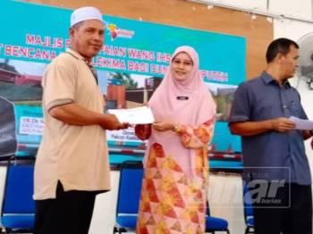 Dr Salmee (dua dari kanan) menyampaikan sumbangan wang ihsan kepada seorang mangsa ribut berkenaan.